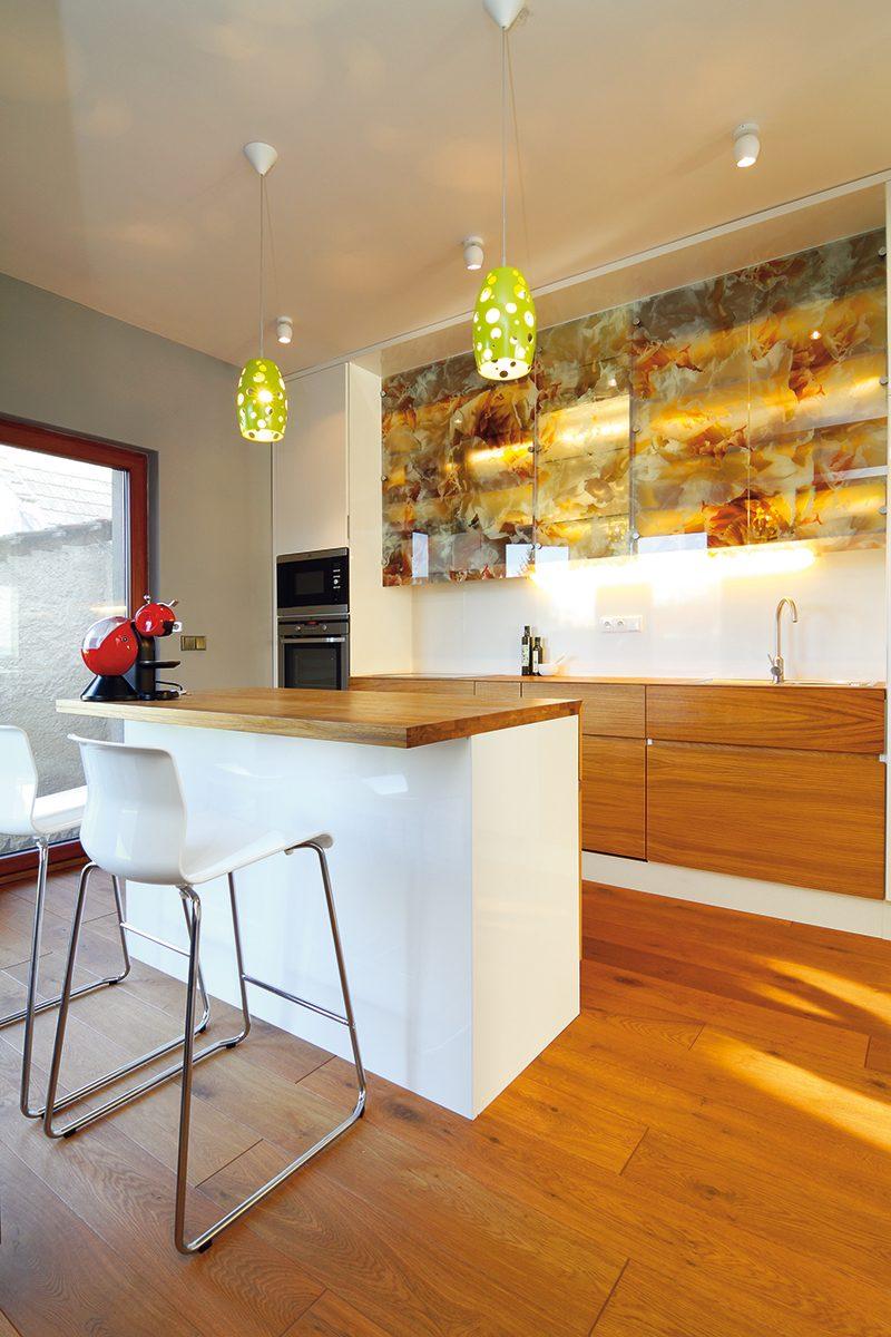 Kuchyň kombinující dřevěnou dýhu, bílé lamino a originální prosklené skříňky s květinovým dekorem je specialitou paní architektky. FOTO: Dano Veselský