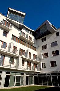 Nepravidelně komponované balkony se zasklením z barevného skla nepochybně upoutají pozornost (architektonická realizace Maxova domu v Bratislavě).