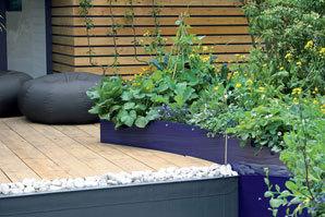 Vkusným prvkem je vyvýšený záhon vsytě modrém podstavci, vněmž rostou bylinky.