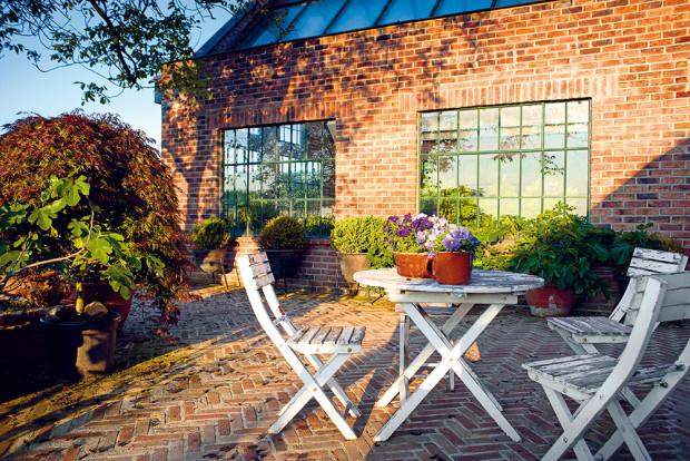 Ve staré anglické zahradě se zimní zahradou z pálených cihel a terasovým dvorkem poskytuje stín starý ořešák. Oprýskané dřevěné židle dodávají místu patinu. Foto: Jiří Tvaroh