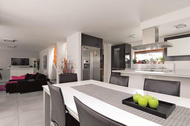 Společenská část domu v přízemí je vyřešena jako otevřený prostor, který plynule přechází od komunikační zóny v místě schodiště přes kuchyň a jídelní kout až do obývacího pokoje.