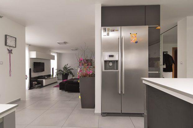 Americká chladnička je součástí polopříčky, která opticky odděluje kuchyň od vstupní a komunikační zóny přízemí. Propojenost jednotlivých zón interiéru je podpořena velkoformátovou šedou dlažbou.