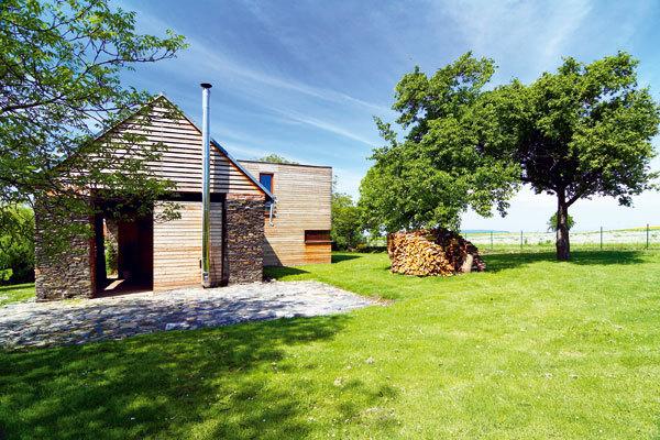 Dřevostavba postavená ve staré kamenné stodole