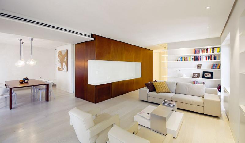 Obývací pokoj je přímo propojen sjídelnou acelému prostoru dominuje kvádr obložený panely zrezavého plechu Corten sbílou rohovou nikou. Kvádr vsobě ukrývá mnoho odkládacích prostorů, přístupných zkaždé strany. FOTO: Anna Galante