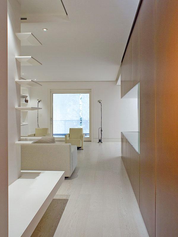 Pohled zchodby do obývacího pokoje. Základem tohoto interiéru byla vzdušnost ahodně světla – jednak přirozeného, přes velká okna, jednak umělého –, které vytváří možná až chladivou, ale čistou atmosféru. FOTO: Anna Galante