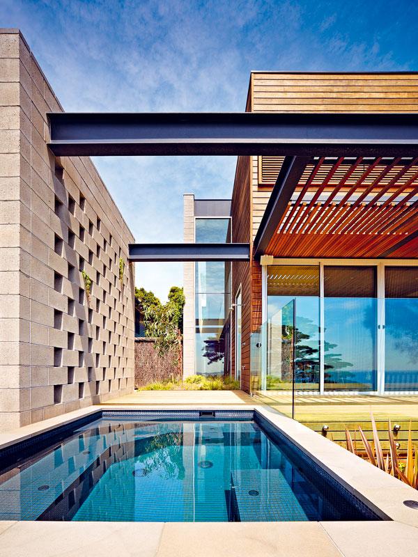 Zajímavým detailem domu je krátký úsek zdi nad úzkým oknem do haly, natřený holubí modrou. Ladí s horizontálami ocelové konstrukce a zároveň umožňuje vyniknout svislici obvodové zdi, která spolu se zdí u bazénu vnáší do kompozice protiváhu. FOTO: Rhiannon Slater