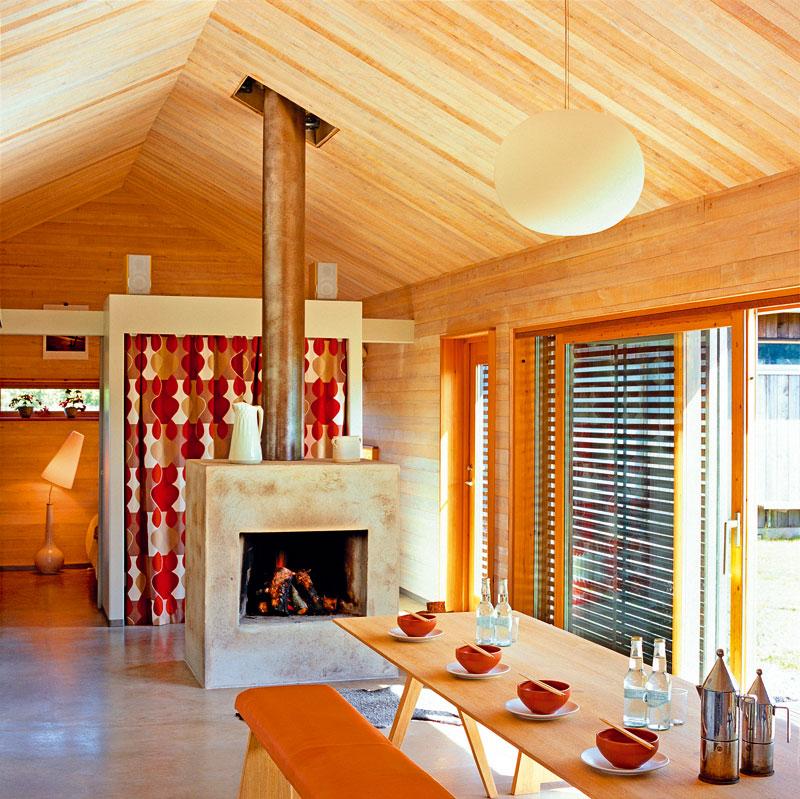Tvar jídelního stolu alavic podporuje dojem velkého prostoru, výrazný komín zvedá pohledy nahoru, kdřevěnému stropu. V hladké betonové podlaze je zabudovaný teplovodní vytápěcí systém. Dlouhý stůl vjaponském stylu je od značky Movitz, lavice navrhli Per Holgesson aNick Ǻberg pro značku Loo Design.