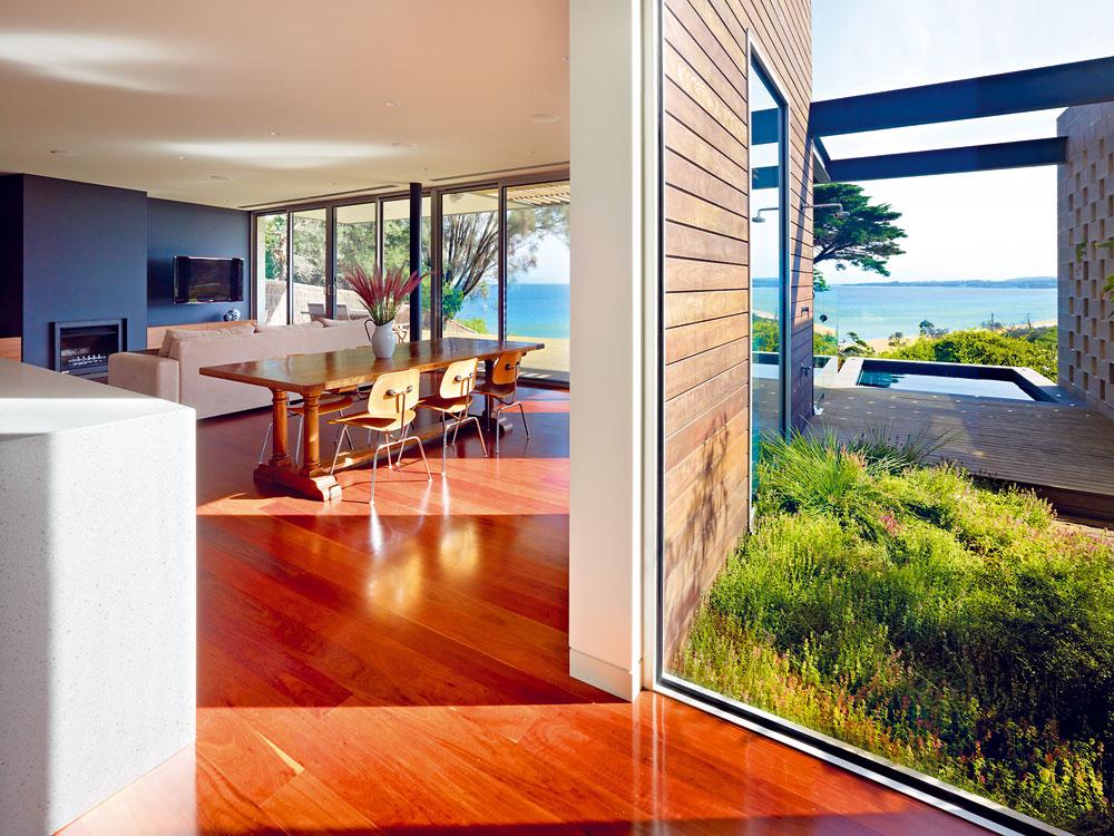 """Obývací pokoj obrácený na sluneční stranu chrání před horkem přibližně dvoumetrový přesah střechy nad terasou. Její podlaha se stává proměnlivým """"plátnem"""", na které maluje světlo. Také na terase vznikají atraktivní odlesky přes rastr otvorů ve zdi vedle bazénu. FOTO: Rhiannon Slater"""