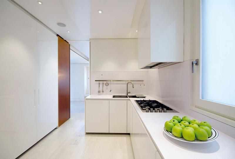 Kuchyň celá oděná do chladivé bílé bez jakýchkoliv rušivých drobností. Vše, co nemá být vidět, je schováno buď vbílých skříňkách, nebo ve velkém úložném prostoru ukrytém za bílými dveřmi vútrobách rezavého kvádru. FOTO: Anna Galante