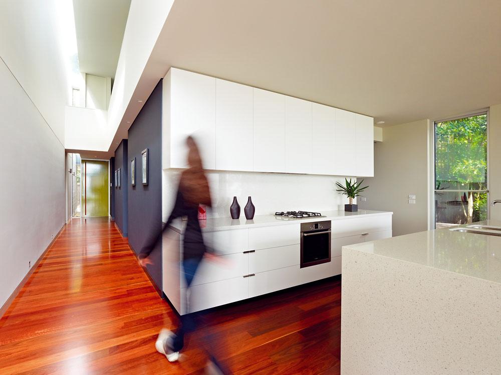 """Nápadný efekt """"vrstvení"""" vytváří strop přerušený světlíkem, bok kuchyňské stěny, příčka v hale, bariéra galerie i její podhled, kde vrstvy podbarvuje bodové osvětlení. Volný prostor mezi východní obvodovou zdí a galerií umožnil umístit vedle vstupu úzké okno přes dvě poschodí. FOTO: Rhiannon Slate"""