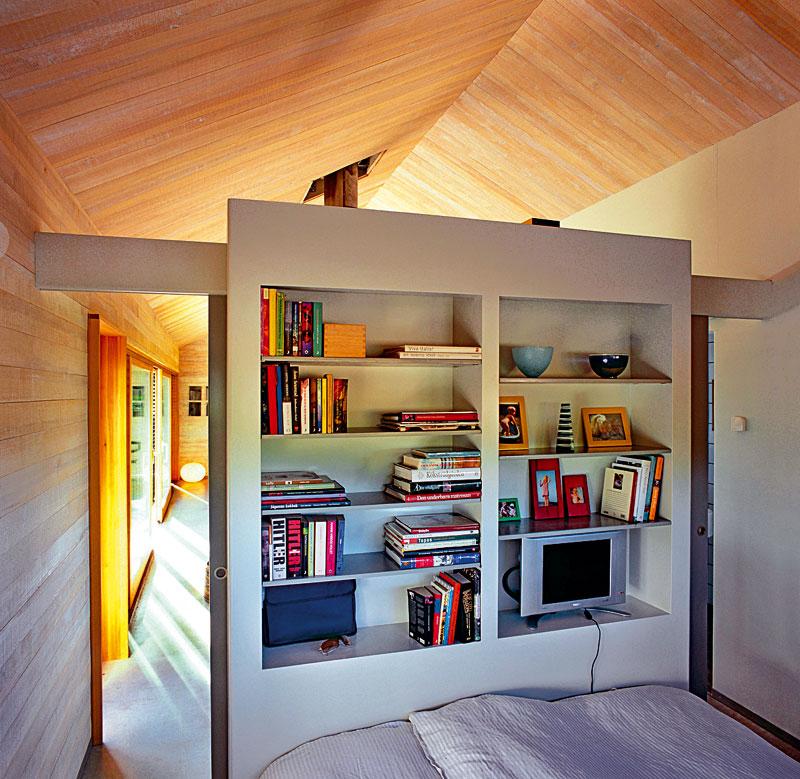 Zadní strana skříně – dělicí příčky zároveň slouží jako police na knihy u postele. Dvoje posuvné dveře umožňují přístup klůžku zedvou stran.