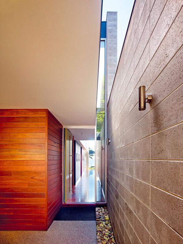 Hlavní trumf domu – výhled – láká už od vstupních dveří. Světlík naplňuje vstupní halu světlem, které se navíc zrcadlí v lesklé podlaze z tmavého dřeva. V nižší vstupní části zároveň poskytuje atraktivní pohled na koruny stromů a oblohu. FOTO: Rhiannon Slate