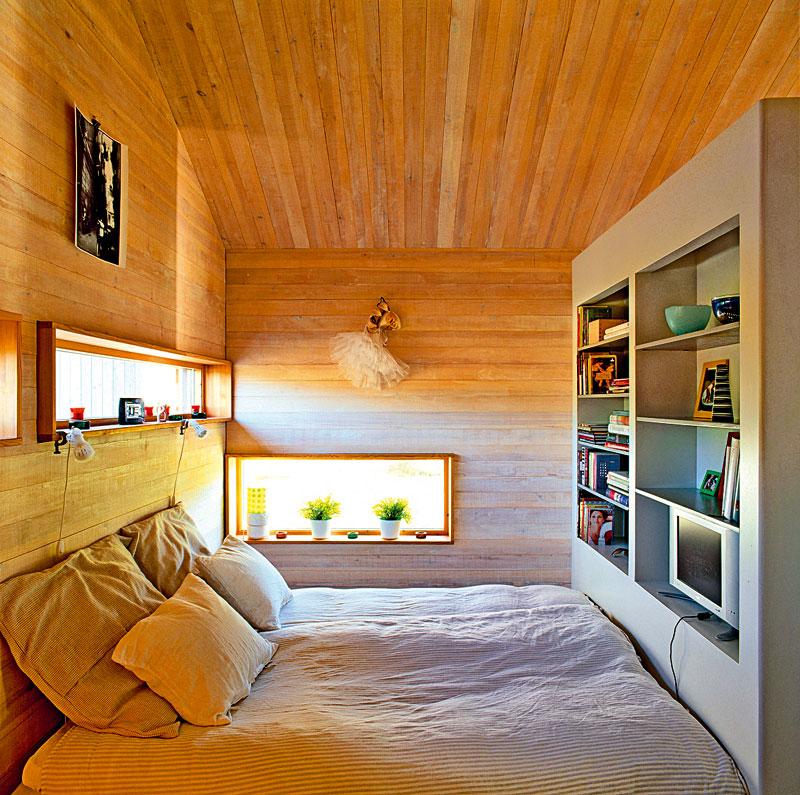 Nízko umístěná okna nabízejí nádherný výhled i zpohodlí postele. Zvláštní dřevěné orámování slouží jako originální polička – ideální místo pro květiny adrobnosti.