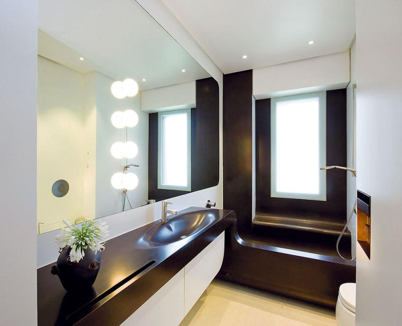 Koupelna, kterou využívají hlavně děti, vdynamickém bílo-čokoládovém vyhotovení má zajímavou vanu, která plní i funkci sprchového koutu. FOTO: Anna Galante