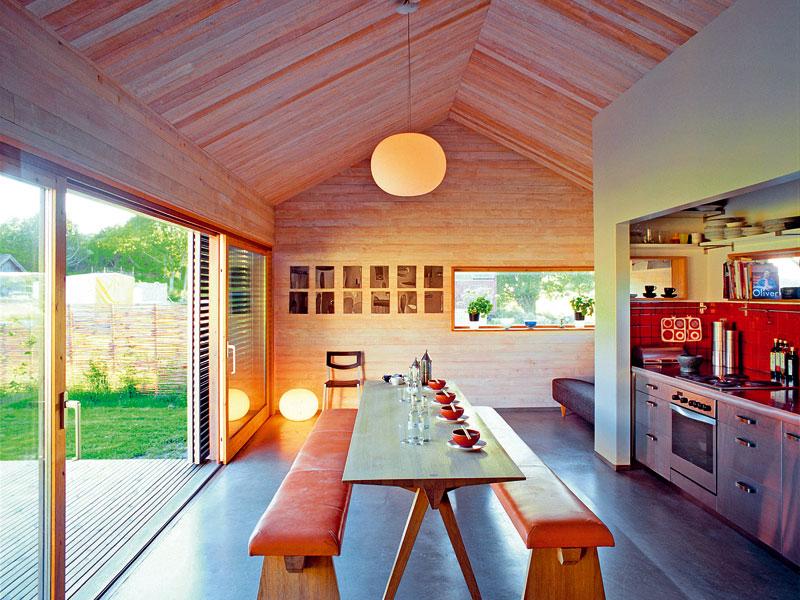 Využitím dřeva, betonu ahladkých bílých omítek se architektovi podařilo vytvořit harmonické kombinace povrchů i zajímavé kontrasty. Nerez vkuchyni se decentně doplňuje sdominantním dřevem azároveň nádherně kontrastuje slesklým jasně červeným obkladem.