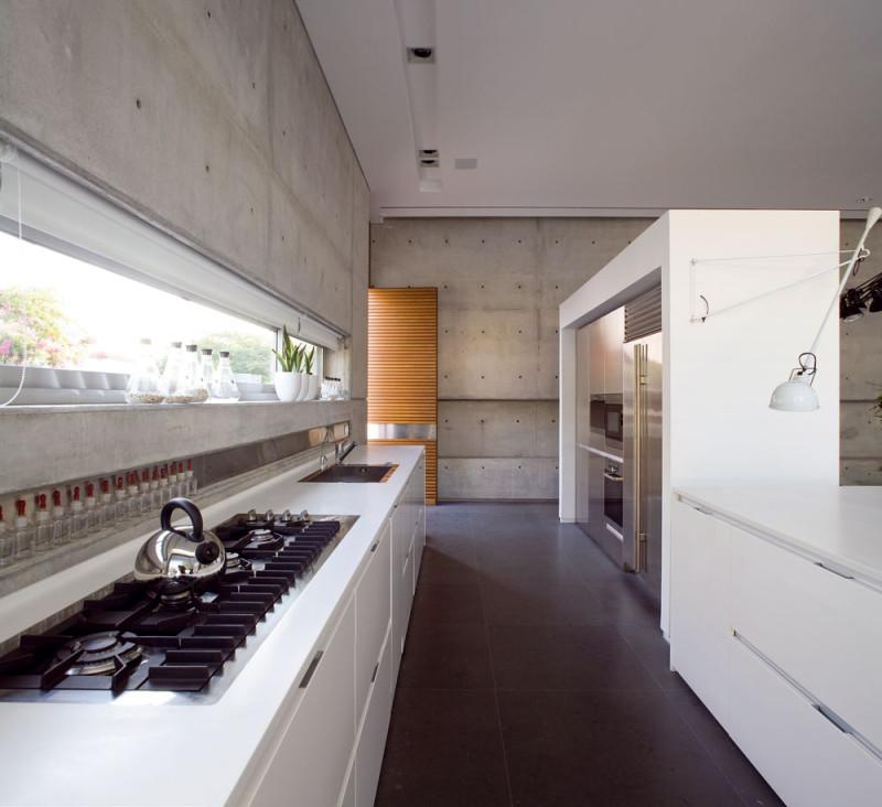 Vkuchyni slouží jako odkládací prostor parapet pásového okna a výřez ve zdi podél pracovní desky. FOTO: Amit Geron