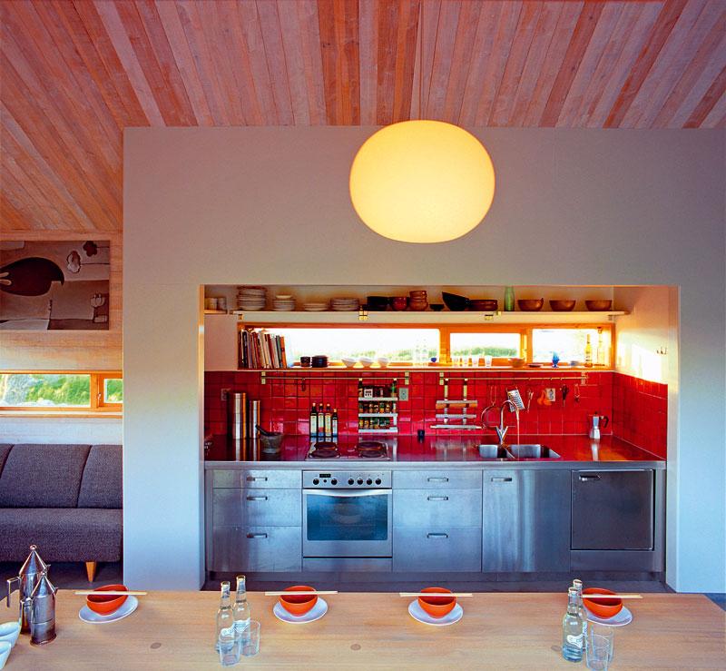 Nerezová tyč umožňuje odkládat kuchyňské pomůcky tak, aby nezabíraly pracovní plochu, apřitom byly vždy na dosah. Okna vnášejí do pracovního prostoru denní světlo, jejich umístění zároveň nabízí možnost využít parapet jako další poličku. Odkládací plochy jsou i na otevřených policích po celé délce kuchyně –umožňují lehký přístup knádobí ake kuchyňským potřebám.