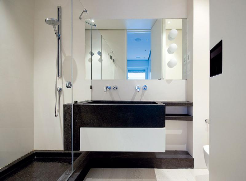 Koupelna u hlavní ložnice vjednoduchých tvarech svyužitím kontrastu bílé na stěnách ačerného mramoru. FOTO: Anna Galante