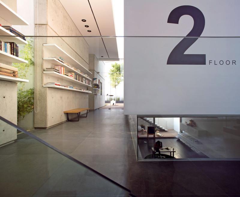 Vyvýšená ložnice umožnila vytvořit u paty zdi skleněný sokl, jímž proudí světlo do dolního obytného prostoru FOTO: Amit Geron
