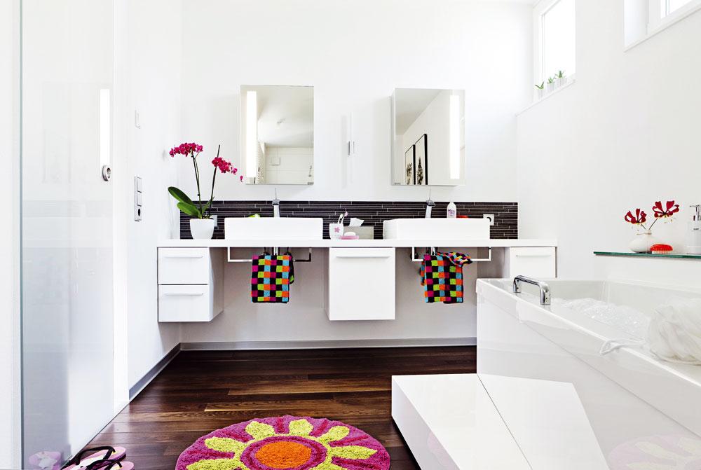 Čistotná dvojčata. Dvě umyvadla zabírají celou čelní stěnu koupelny. Pod praktickou deskou s lesklým povrchem jsou umístěny skříňky se zásuvkami, do nichž lze uložit vše, co souvisí s každodenní hygienou. Prostor přímo pod umyvadly je záměrně volný – můžete tak u umyvadla pohodlně stát bez toho, abyste nohama do něčeho naráželi. Jako ochrana stěny před stříkající vodou slouží úzký pás obkladaček.