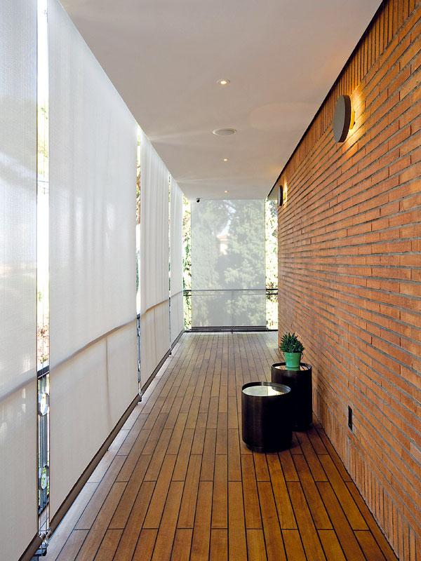 Velký balkon obklopuje obývací pokoj. Pro vytvoření soukromí azastínění před ostrým římským sluncem využily architektky jemnou textilii, kterou je možné svinout a ukrýt do podhledu balkonu, není-li jí třeba. FOTO: Anna Galante