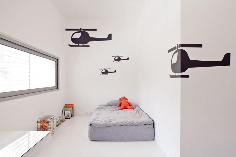 Pásové okno v severnějším zedvou dětských pokojů je situované vlinii očí. Pop-artová grafika, typická pro celý dům, se tu projevila v šablonové stylizaci dekoru na stěnách. FOTO: Amit Geron