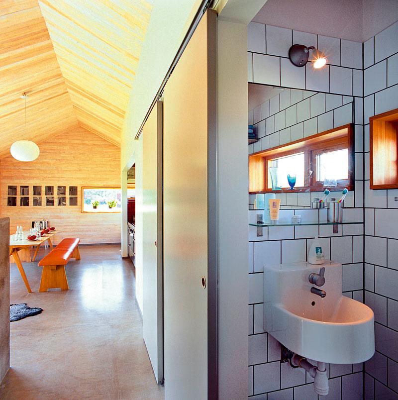 """Dlažba z portugalského kamene definuje oblast toalety akoupelny, které jsou od obytné části odděleny šedými posuvnými dveřmi zdřevovláknitých desek. Šedou dlažbu vyvažují klasické bílé obkladačky uložené """"na vazbu""""."""