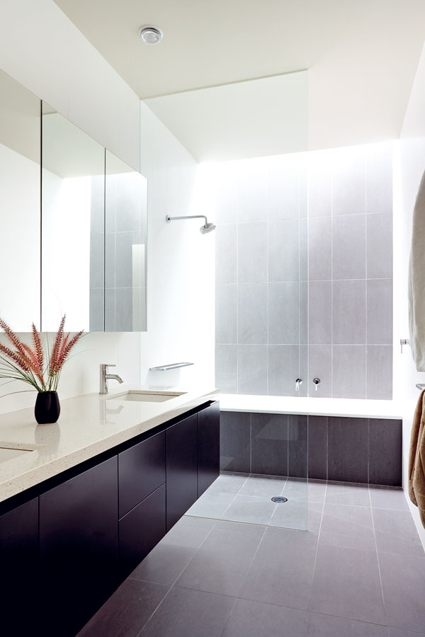 Obě koupelny v poschodí jsou osvětlené přes úzký světlík. Koupelna s mycím pultem z téhož materiálu, z jakého zhotovili kuchyňský ostrov, patří k dětským pokojům. FOTO: Rhiannon Slater