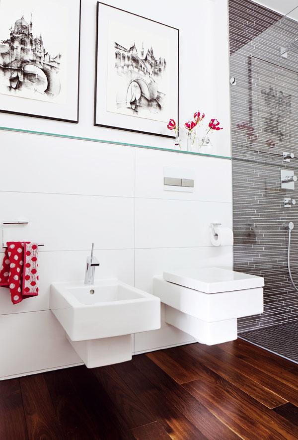 V soukromí. Skryté za nízkou stěnou jsou v prostoru mezi vanou a sprchou závěsné WC i bidet (Duravit). Všechny prvky sanitární keramiky v koupelně jsou z jedné série, takže jejich tvary spolu dokonale ladí.