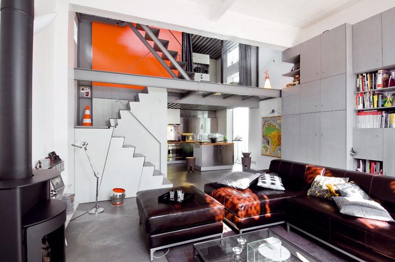 Šedá barva vprostoru jasně dominuje. Majitelé však na část stěny zvolili výraznou oranžovou apoužili i více zářivých doplňků, čímž prostor rozzářili. FOTO: JULIEN CLAPOT, PHOTOFORPRESS