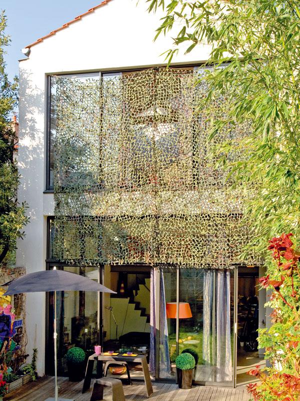 Před zvědavými pohledy sousedů jsou velká okna chráněna ochrannou sítí, která dům kryje zvenčí. Umožňuje přitom nerušený pohled do zahrady anebrání přístupu světla. U domu nechybí vlastní kus zeleně. Zahrada má jen 60m2, ale potřebám majitelů plně postačuje. FOTO: JULIEN CLAPOT, PHOTOFORPRESS