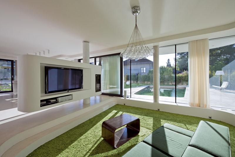 Obývací pokoj akuchyň od sebe odděluje jen bílá nábytková hmota – zjedné strany je na ní umístěna televize, zdruhé slouží jako vitrína vjídelně. Nosný prvek nábytku byl využit i k vedení komínu ke krbu. FOTO: Hertha Hurnaus