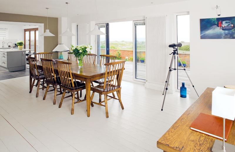 Ve velkém bílém prostoru s charakterem minimalismu, nezahlceném množstvím věcí, dřevěný stůl ažidle spatinou aduší venkova prostor ohřívají avnášejí do něj prvek domova. FOTO: CARLOS DOMINGUEZ