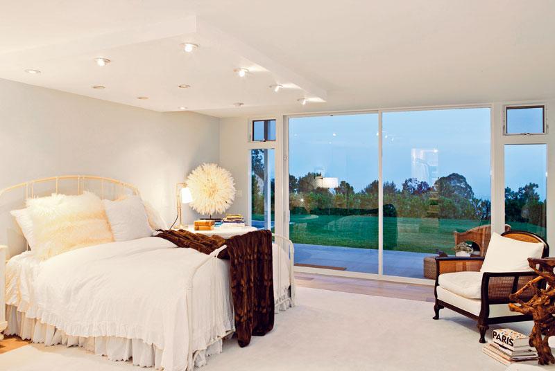 Na terasu a k bazénu se dá vyjít ze všech důležitých prostorů v domě. Okna na celou výšku místnosti a nádherný výhled dodávají příjemnou atmosféru také ložnici. Elton John a jeho manžel si ji zařídili v eklektickém stylu. foto: isifa
