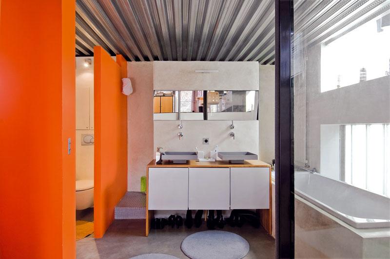 Prostorná koupelna je podobně jako celý dům díky velkým oknům krásně světlá. Zvědavým pohledům brání mléčné sklo. Toaleta je od zbytku koupelny oddělena příčkou. Za ni majitelé umístili i prádelnu. FOTO: JULIEN CLAPOT, PHOTOFORPRESS
