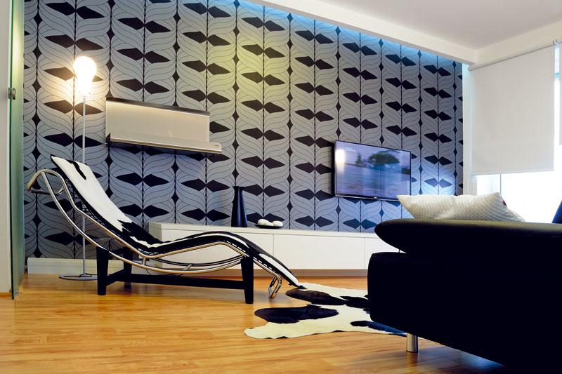 Celý byt je zařízen jednoduše a minimalisticky. Trochu rozruchu a ornamentálnosti vnášejí do interiéru jen graficky výrazné tapety. Vobývacím pokoji vytvářejí pozadí pro televizi a krb, vložnici zase pro postel. Vpředsíni pak oblékly šachtu, vníž se skrývá odvětrávací systém digestoře. Foto: Soňa Chlumecká pro Live Design