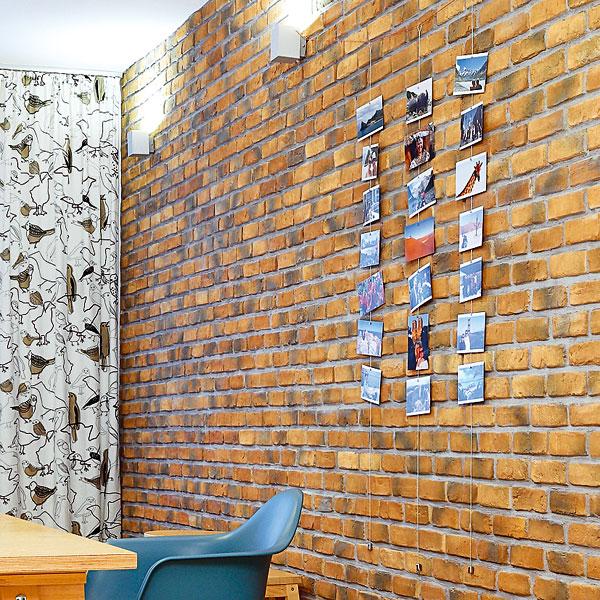 Vlastnoručně vyrobená dekorace na cihlové stěně. Fotografie z cest na ocelových lankách s těžítky na koncích. FOTO: DANO VESELSKÝ