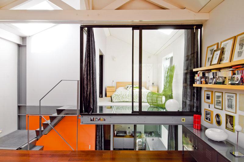 Otevřená koncepce bydlení, vjejímž rámci jsou místnosti odděleny jen skleněnými příčkami adveřmi, není pro každého. Majitelům však plně vyhovuje. A když přece jen potřebují trochu soukromí, stačí zatáhnout závěs. FOTO: JULIEN CLAPOT, PHOTOFORPRESS
