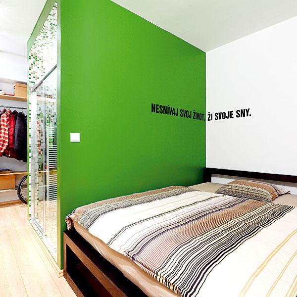 Ložnice se nachází za koupelnou a kuchyňskou linkou, jejíž zadní stranu tvoří šatna. Zelená olejová barva, kterou je zvýrazněn blok koupelny, pokračuje i v ložnici. Architekti měli radost z nápadu majitelky – napsat své krédo na stěnu. FOTO: DANO VESELSKÝ
