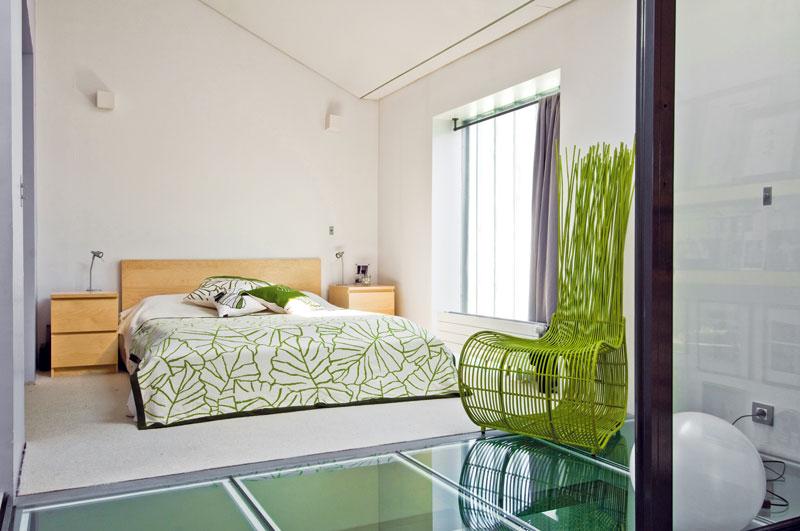 Vložnici majitelé zvolili svěží zelenou barvu. Podobně jako koupelna se zavírá zasklenými posuvnými dveřmi. Nechtěli ji zatížit nábytkem, proto vní najdete jen postel, noční stolky akřeslo na čtení. FOTO: JULIEN CLAPOT, PHOTOFORPRESS