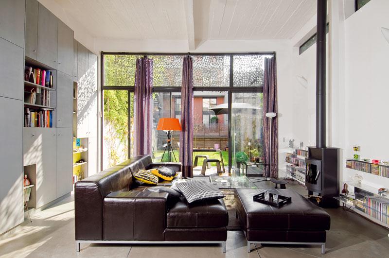 Díky vysokým stropům působí obývací pokoj vzdušně. Dominuje mu obrovská kožená sedačka na kovových nožkách. Ovětší pohodlí se starají polštáře srůznými motivy. Vedle kamínek na dřevo ve skandinávském stylu majitelé umístili velmi nízké police zohýbané oceli. FOTO: JULIEN CLAPOT, PHOTOFORPRESS