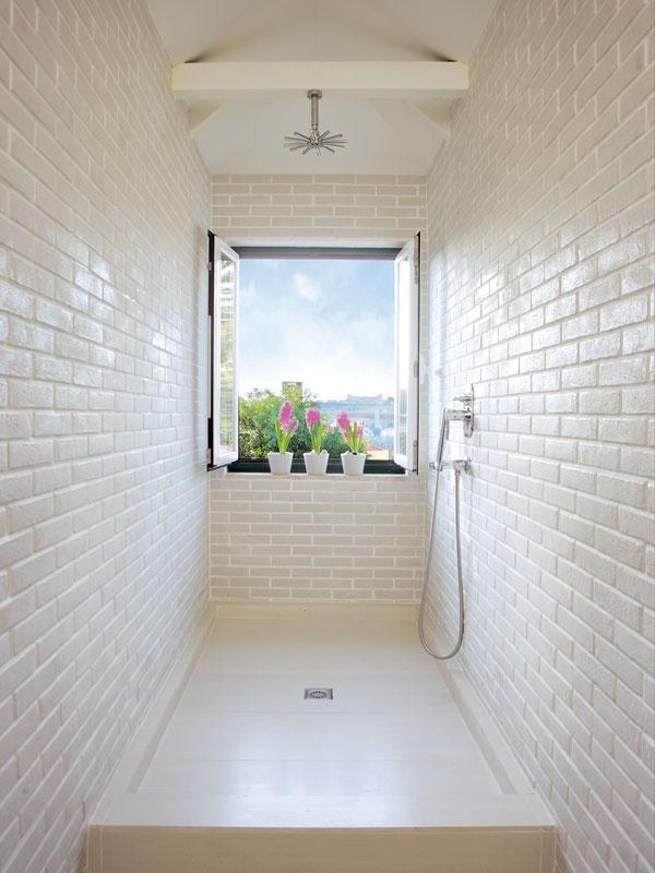 Velkorysý sprchový kout není od zbytku koupelny oddělen zástěnou ani závěsem. Okno v koupelně nezakrývají závěsy, otvírá se přímo do světa. Protože Filipa nemá sousedy, kteří by mohli vidět do jejího bytu, užívá si luxusu soukromí.  FOTO: Photoforpress