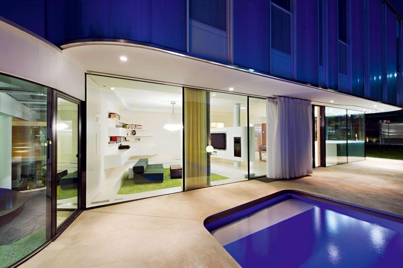 Po setmění se exteriérové osvětlení postará o nové zážitky ze zahrady: odraz světla zpod hladiny bazénu zabarví původně bílou fasádu do modra a světlo v interiéru spolu snasvícením přesahujícího poschodí ještě více zvýrazní propojení interiéru s exteriérem. Tuto atmosféru umožnila předsazená fasáda zlexanových panelů uložených do hliníkového rámu. FOTO: Hertha Hurnaus