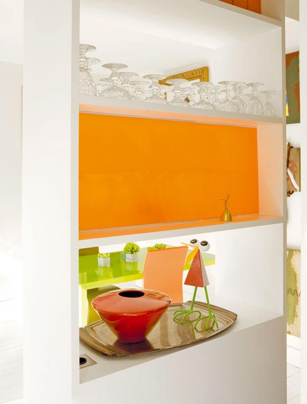 Některé police jsou přístupné z obou stran, jiné jsou z jedné strany uzavřené tabulemi oranžového plastu. Tyto průhledné barevné akcenty rozjasňují malý prostor a odkazují na oranžový nábytek.