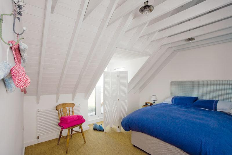 Ložnice pro hosty je stejně jako ostatní ložnice zařízena minimalisticky. Nachází se vní jen to, co skutečně potřebujete. Dominantou prostoru je jen dřevěná konstrukce krovu natřená na bílo. FOTO: CARLOS DOMINGUEZ