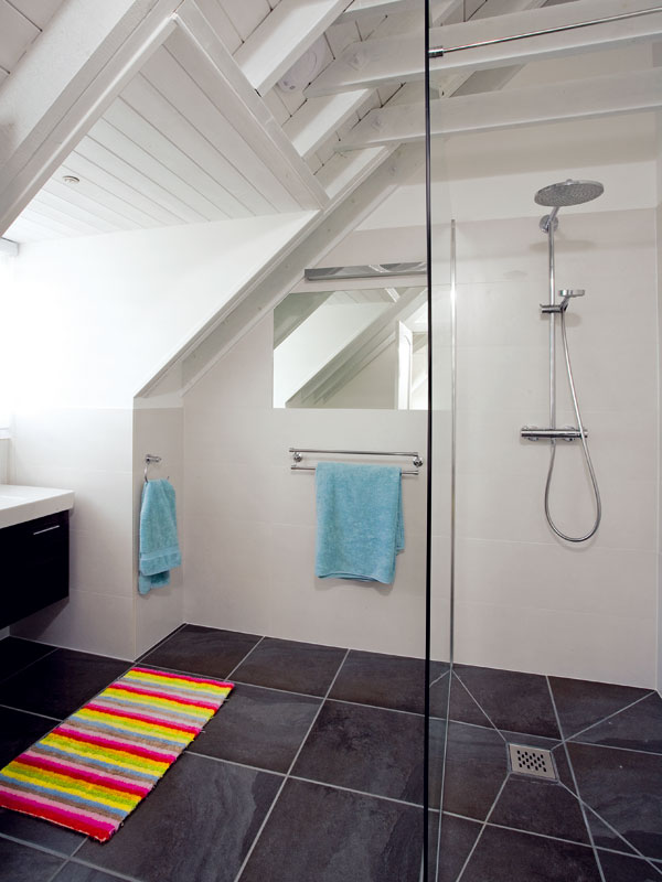 V poschodí jsou tři koupelny, všechny vtomtéž duchu, sbílým kabátem na stěnách ačernými botami na podlaze. Minimalistický design nechává vyniknout výrazným prvkům dřevěné konstrukce šikmé střechy. FOTO: CARLOS DOMINGUEZ