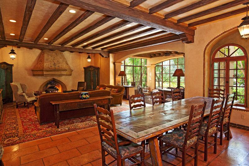 V rustikálním prostoru obývacího pokoje s jídelnou je typicky venkovská dlážděná podlaha a stropy z nahrubo otesaných dřevěných trámů, nechybí ani monumentální krb. foto: isifa