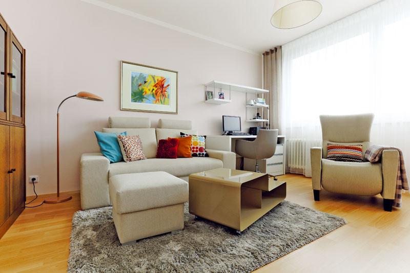 Stejně jako velká část bytu je i obývací pokoj zařízen vtlumených přírodních odstínech: hnědé, šedé, béžové a krémové. Sytější barvy vnášejí do interiéru jen textilní doplňky. Foto: Dano Veselský