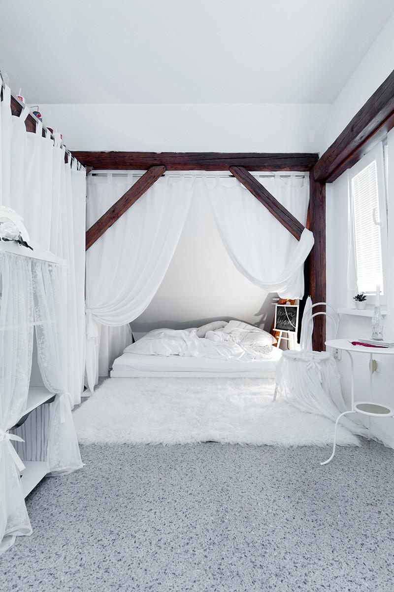 """Za komínem a bílým závěsem je Nikolina princeznovská ložnice, s postelí vyrobenou ze staré skříně. """"Ta postel je taková má vysněná. Jsem vysoká, a tak jsem si poručila dvě matrace, abych měla dost místa na nohy i na ruce. I ta kožešina je velmi užitečná, protože občas mám takové medvědí vstávání – ráno se sotva vykutálím po čtyřech z postele,"""" zazubí se. FOTO: Dano Veselský"""