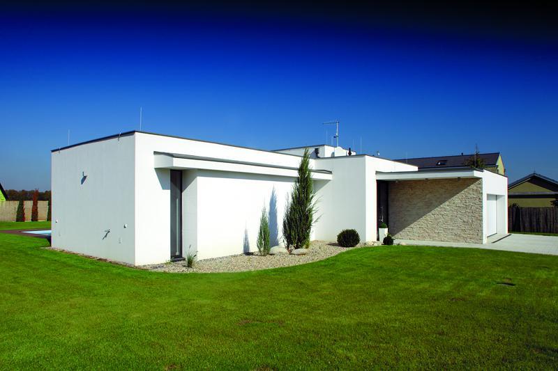 Směrem k ulici vystupuje z jednoduše tvarovaného domu dvojgaráž, která zároveň pomáhá vytvořit chráněný prostor před vstupními dveřmi.